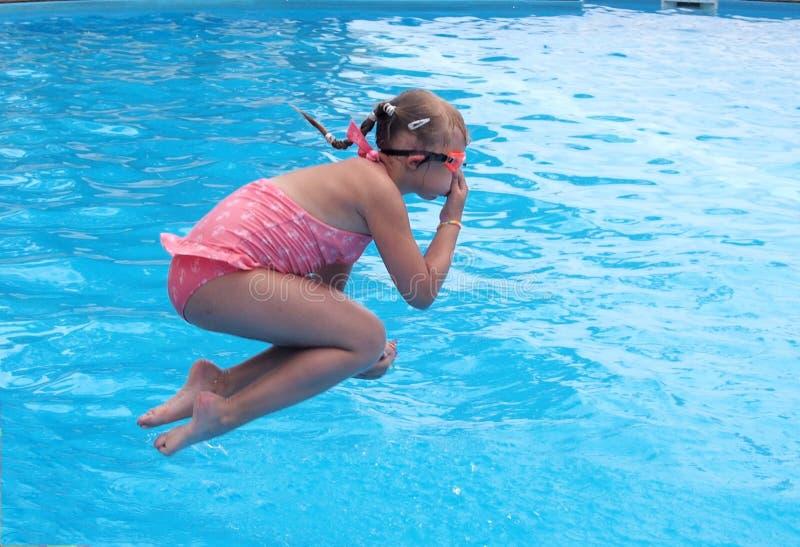 Das Mädchen springend in einen offenen Swimmingpool stockbilder