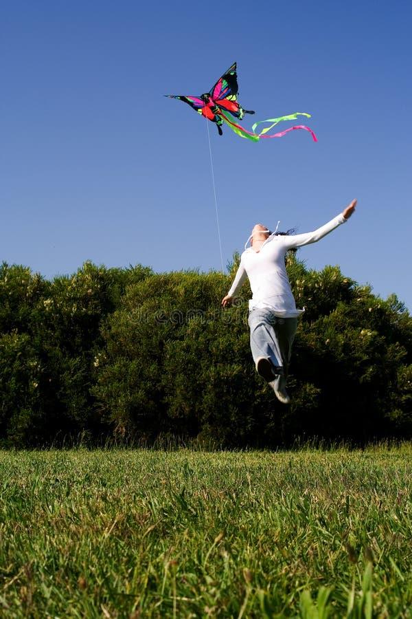Das Mädchen springend mit Drachen lizenzfreie stockbilder