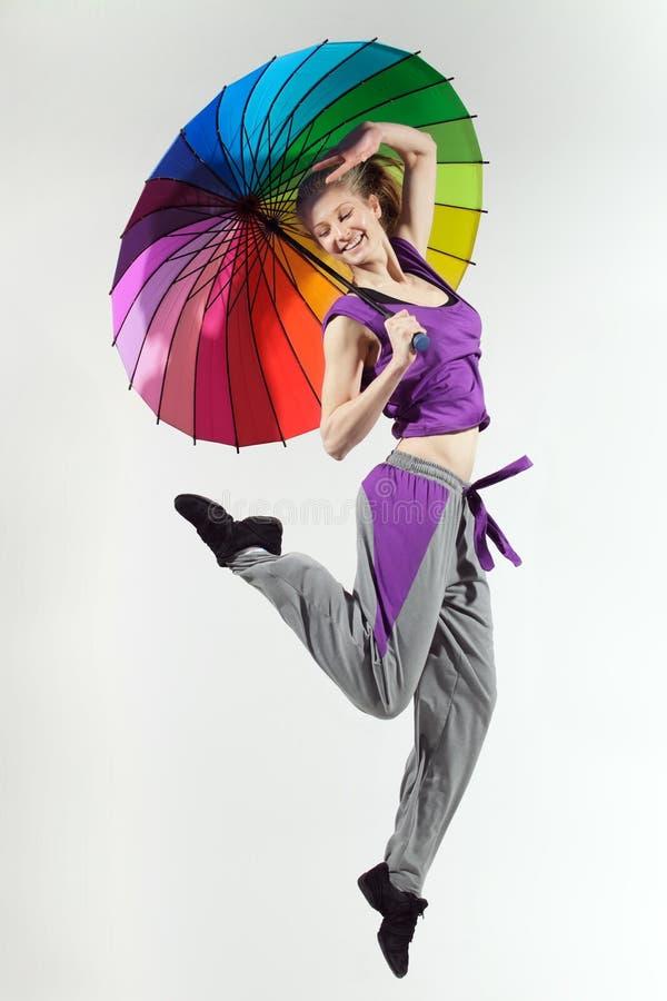 Das Mädchen springend mit Regenschirm stockfoto