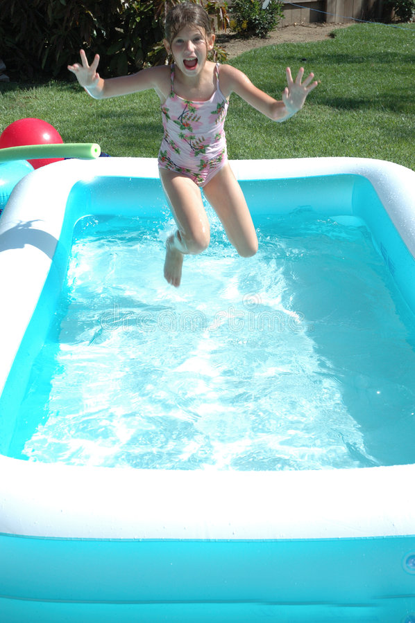 Das Mädchen springend in Pool lizenzfreie stockfotos