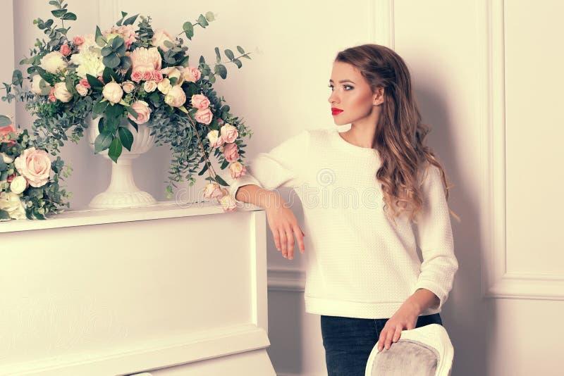 Das Mädchen steht nahe bei einem weißen Klavier stockfoto
