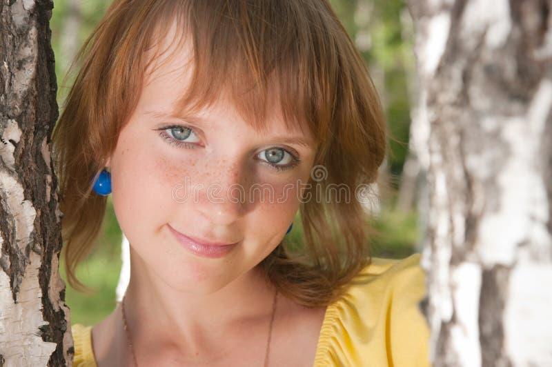 Das Mädchen steht nahe zu einer Birke stockfoto
