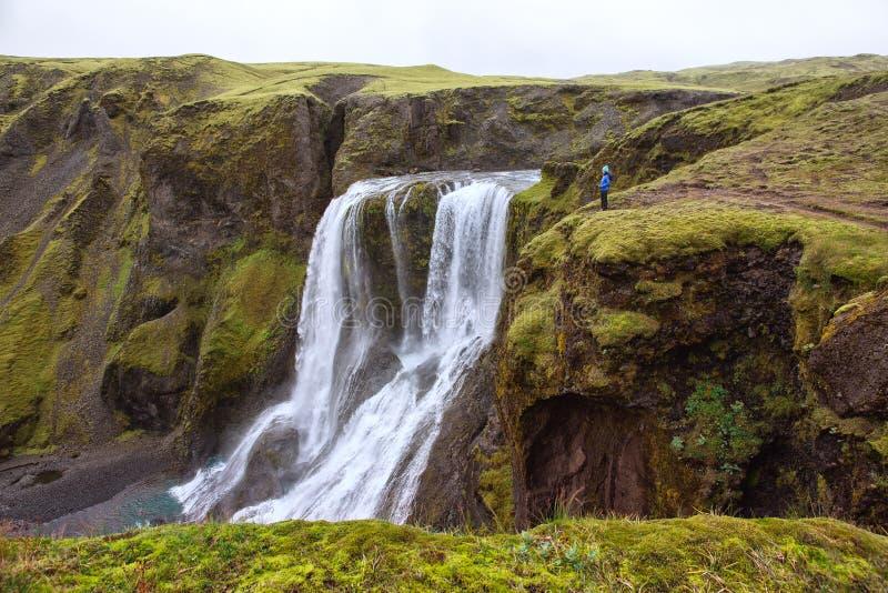 Das Mädchen steht am Rand der Schlucht am Wasserfall Fagrifoss lizenzfreies stockfoto