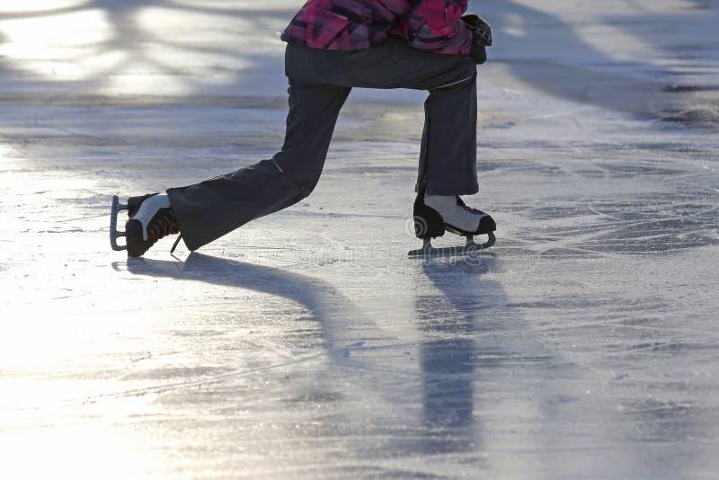 Das Mädchen steigt nach einem Fall eislaufend auf die Eisbahn lizenzfreie stockbilder
