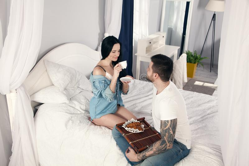 Das Mädchen trinkt Morgenkaffee, der ihr geliebter Ehemann geholt zum Bett sie sind sehr glücklich stockfotos