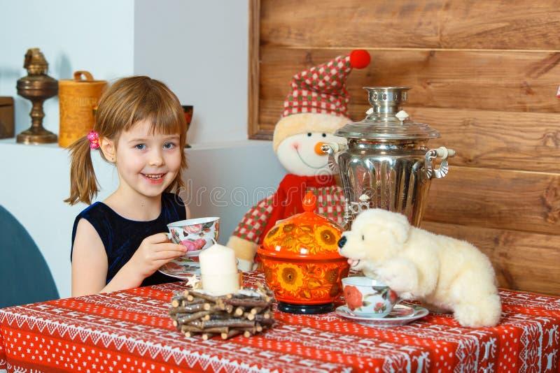 Das Mädchen trinkt Tee und das Lächeln stockfoto