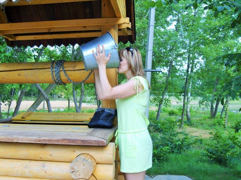 Das Mädchen trinkt Wasser von einem Eimer lizenzfreie stockfotografie