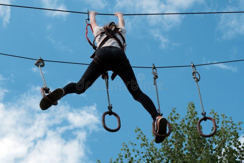 Das Mädchen tritt von einem Ring zu anderen auf einem Streifen von Hindernissen über den Bäumen gegen den Himmel mit Wolken Extre stockfoto