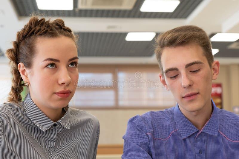 Das Mädchen und der Kerl sitzen nahe traurigen Gesichtern lizenzfreie stockfotografie