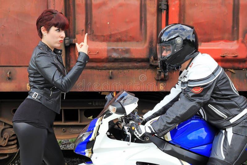 Das Mädchen und der Motorradfahrer stockbild