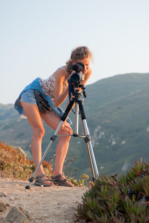 Das Mädchen untersucht die Kamera anbrachte an einem Stativ auf einem Hintergrund von grünen bewaldeten Bergen an einem sonnigen  stockfotos