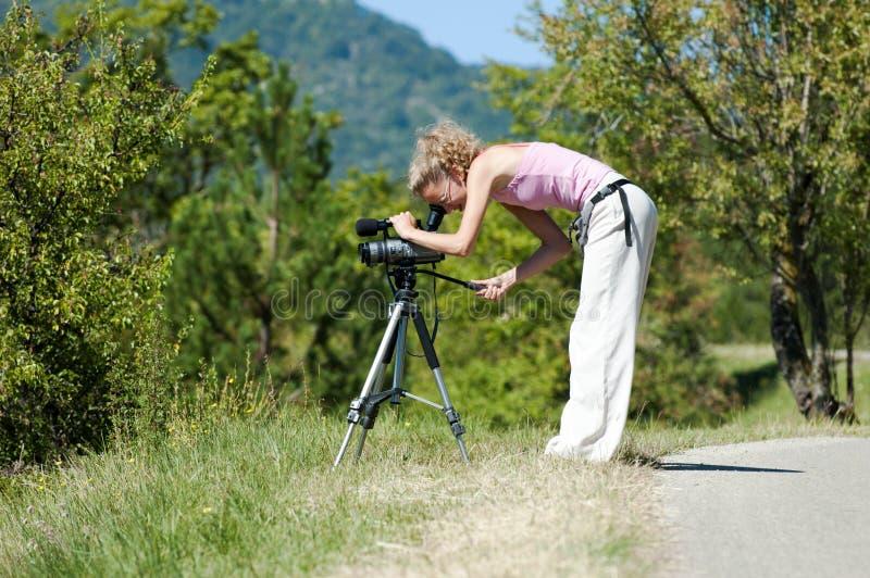 Das Mädchen untersucht die Kamera auf einem Stativ auf dem Hintergrund von grünen Bäumen und von Bergen an einem sonnigen Sommert stockbilder