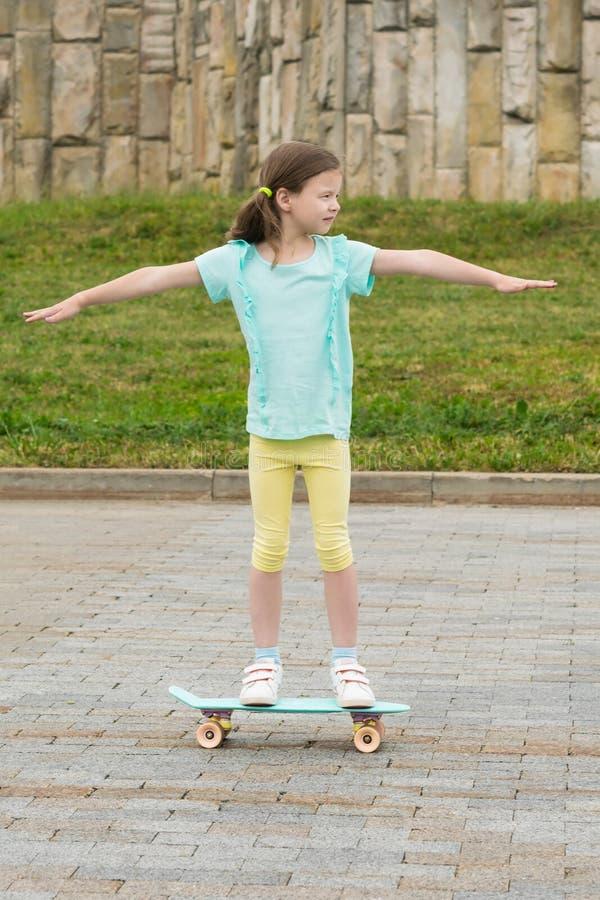 Das Mädchen verbreitete ihre Arme weit und Fahrten auf ein Skateboard im Stadtpark lizenzfreie stockfotografie
