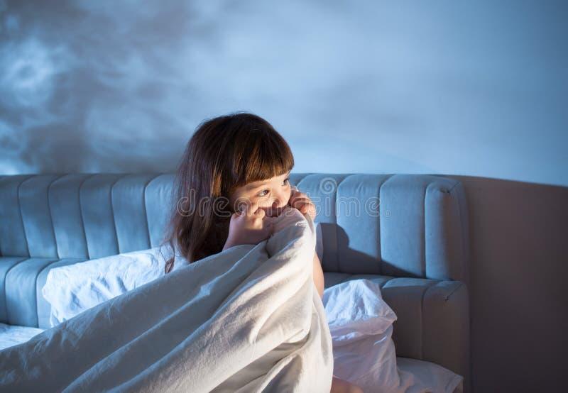 Das Mädchen versteckt ihr Gesicht in einer Decke im Bett nachts lizenzfreie stockfotos