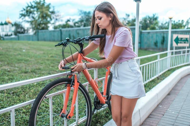 Das Mädchen verteidigt ihr Fahrrad im Park im Sommer Entfernt vom Parkplatz, benutzt eine schützende Kette, stellt das Passwort e stockfotografie