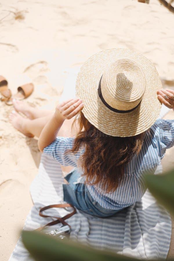 Das Mädchen von der Rückseite im Hut sitzt auf dem Sand stockfotos