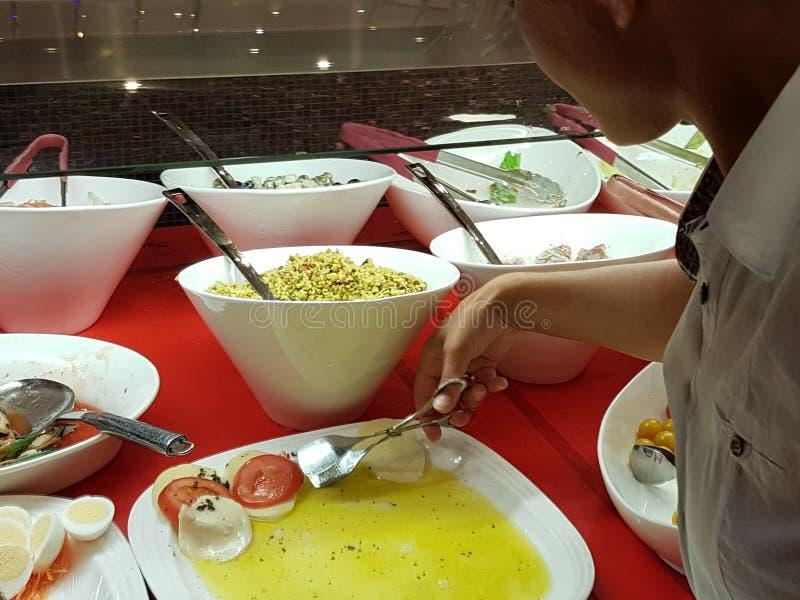 Das Mädchen wählt Lebensmittel in einem asiatischen Restaurant Lohn-was-Sie-wünschen wählt unter den zahlreichen egozotic Tellern lizenzfreie stockfotos