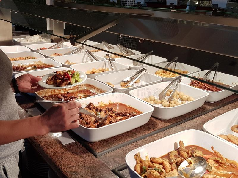 Das Mädchen wählt Lebensmittel in einem asiatischen Restaurant Lohn-was-Sie-wünschen wählt unter den zahlreichen egozotic Tellern stockfotos