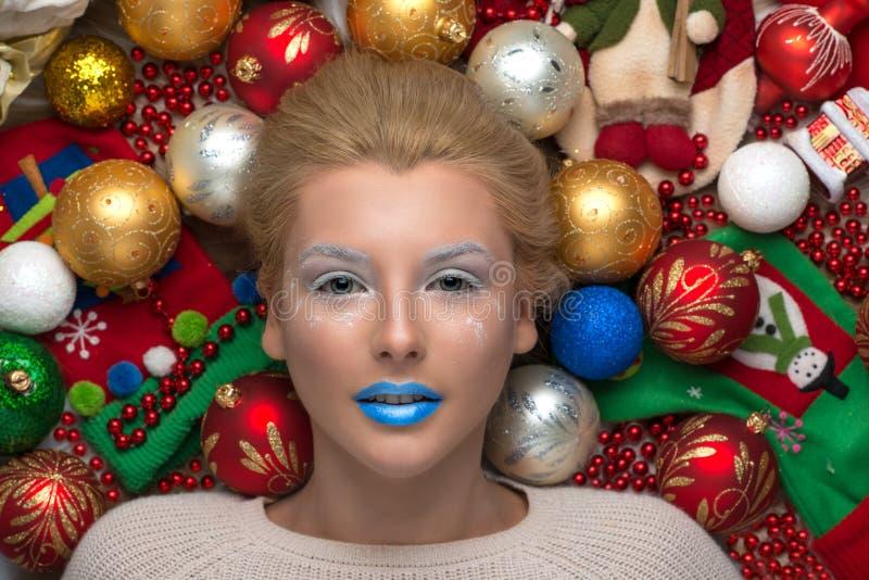 Das Mädchen wird mit Weihnachtsbaumdekorationen umgeben stockbild