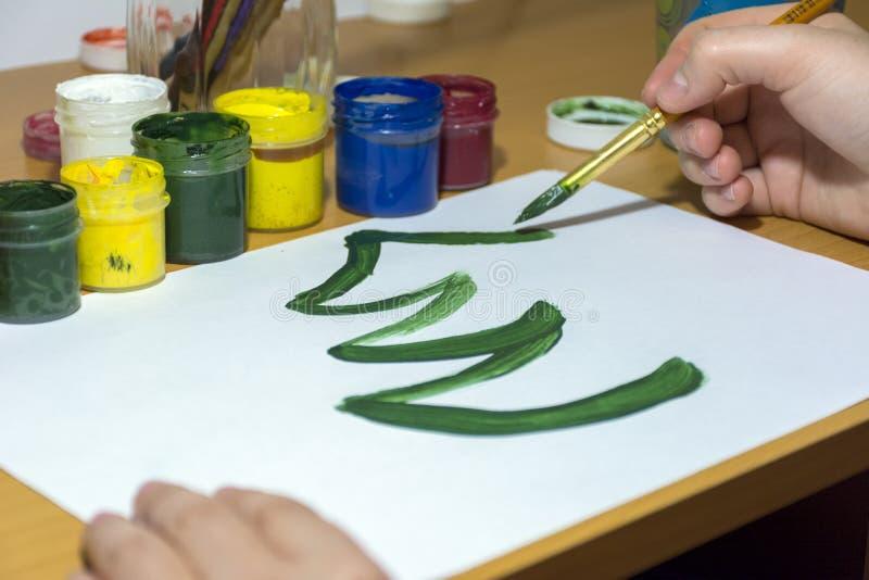 Das Mädchen zeichnet einen Weihnachtsbaum mit Farben auf einem Blatt Papier stockbild