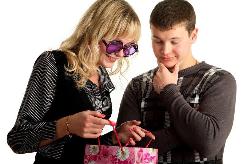 Das Mädchen zeigt Paket kaufend zu ihrem boyfri lizenzfreies stockfoto