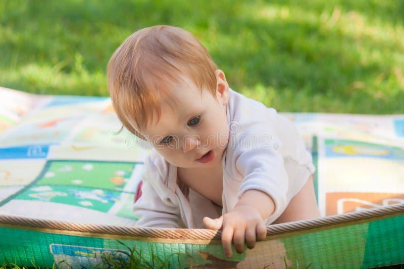 Das Mädchen zieht über den Rand der Wolldecke und betrachtet unten dem Gras stockbild