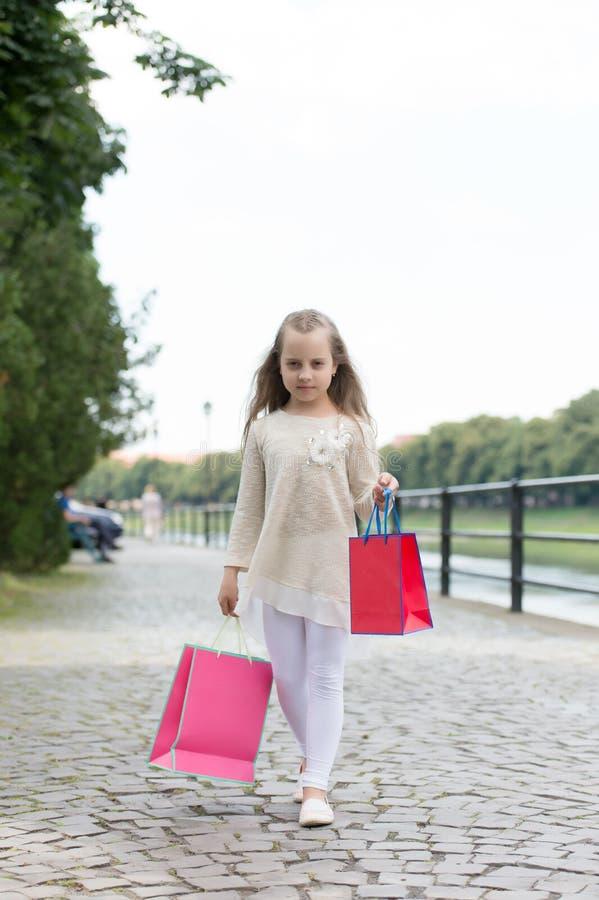 Das Mädcheneinkaufen auf ruhigem Gesicht trägt Taschen, städtischen Hintergrund Scherzen Sie Mädchen mit dem langen Haar, das in  stockfotos