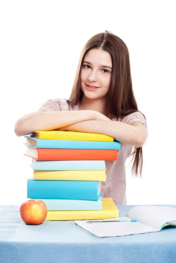 Das Mädchenkind am Tisch mit Büchern lizenzfreie stockbilder