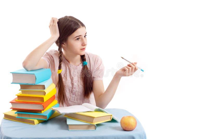 Das Mädchenkind am Tisch mit Büchern stockfotografie