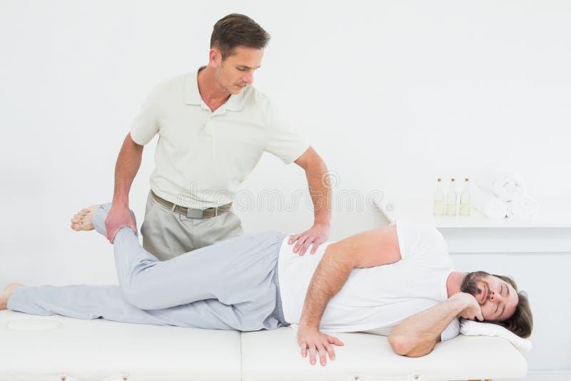 Das männliche Physiotherapeutenausdehnen bemannt Bein lizenzfreie stockfotografie