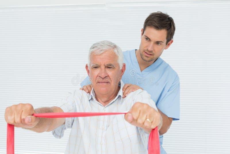 Das männliche Physiotherapeutenmassieren älter bemannt zurück lizenzfreie stockbilder