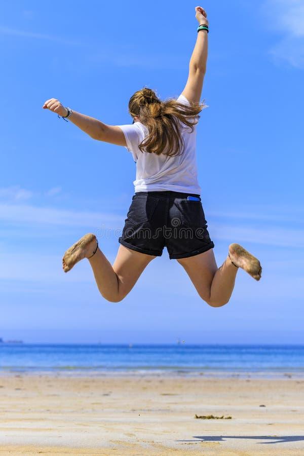 Das M?dchen springend auf den Strand lizenzfreie stockfotos