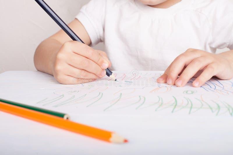 Das M?dchen zeichnet in farbige Bleistifte stockfoto