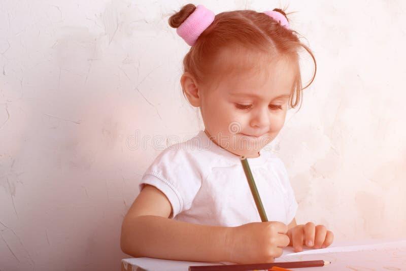 Das M?dchen zeichnet in farbige Bleistifte stockbilder