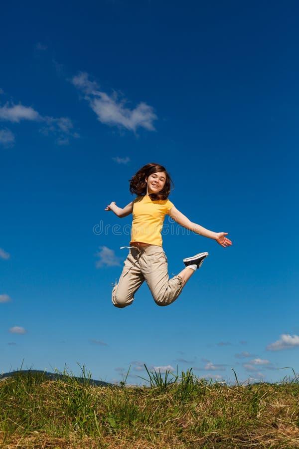 Das M?dchenspringen und l?uft gegen blauen Himmel stockfotos