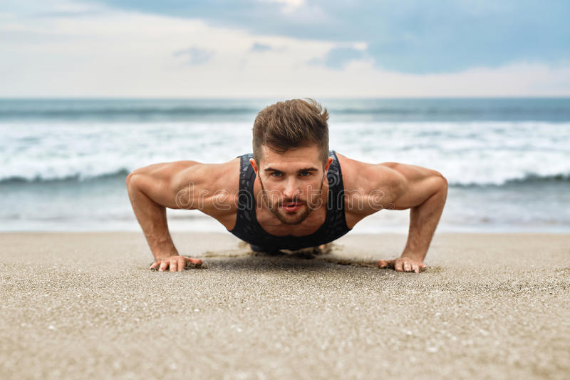 Das Mann-Trainieren, tuend drücken Übungen auf Strand hoch Eignungstraining lizenzfreies stockfoto