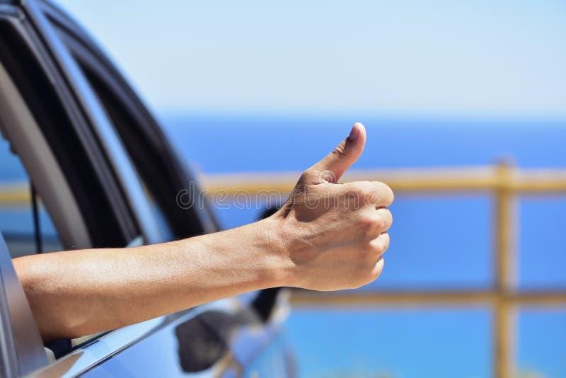 Das Manngeben Daumen unterzeichnen oben herein ein Auto nahe dem Ozean stockfotos
