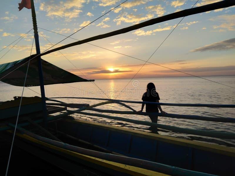 In das Meer allein schwimmen, das den Sonnenuntergang aufpasst, auf einem Bootsmädchen zu sitzen lizenzfreie stockfotos