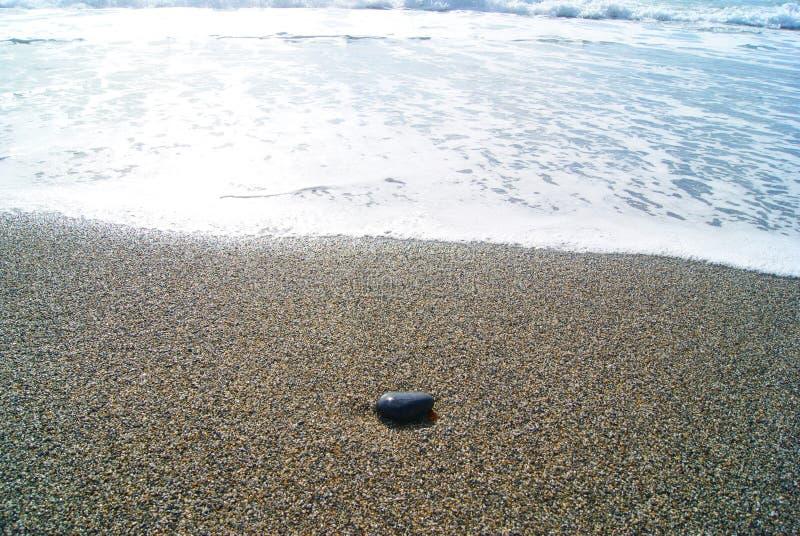 Das Meer und der schwarze Stein im Sand lizenzfreie stockbilder
