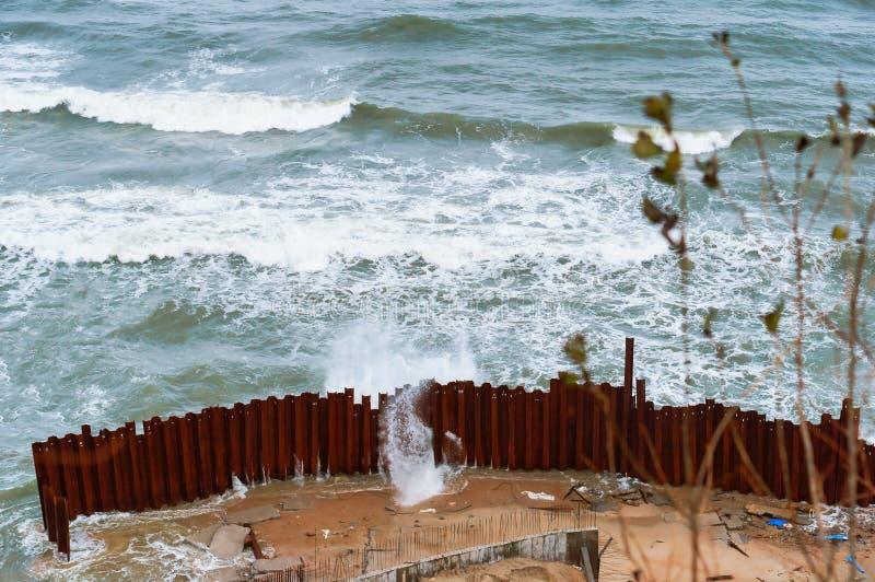 Das Meer und der Sturm, die Wellen brechen über das Fechten lizenzfreie stockfotos