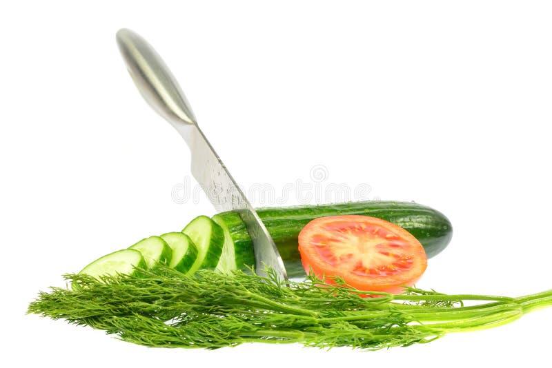 Das Messer schnitt Gurke in Scheiben nahe bei einer halben Tomate und einem Dill stockfotografie