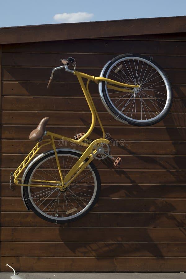 Das moderne Fahrrad, das draußen an der hölzernen Wand des Hauses hängt stockfoto
