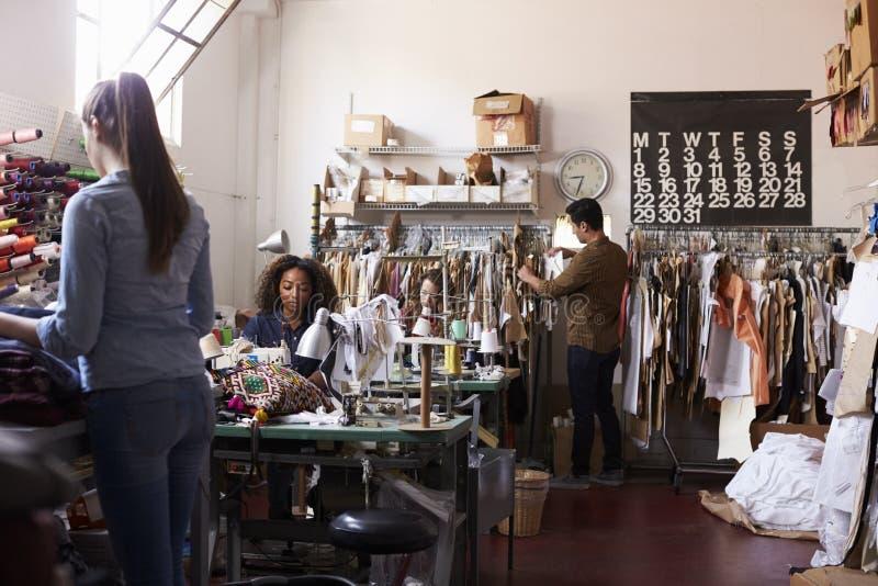 Das multi ethnische Team, das in der Kleidung zusammenarbeitet, entwerfen Studio stockfoto