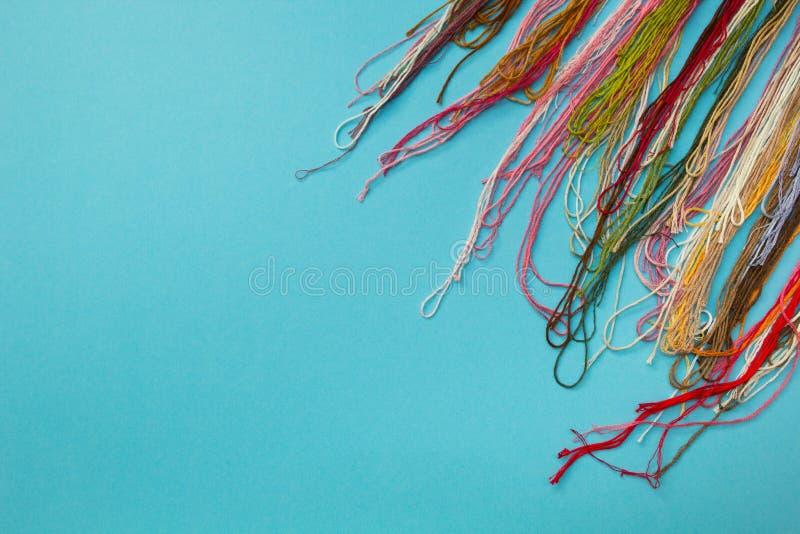 Das multi farbige Garn benutzt für das Stricken von Kleidung auf blauem gestreiftem Hintergrund stockbild
