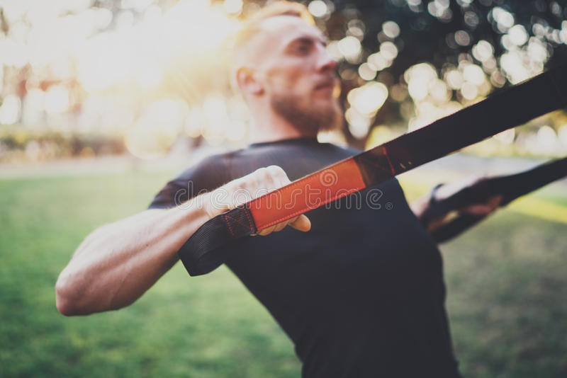 Das muskulöse Athletentrainieren drücken sich oben draußen sonnigen Park am Morgen ein Attraktiver fittness Mann, der Übungen tut stockfoto