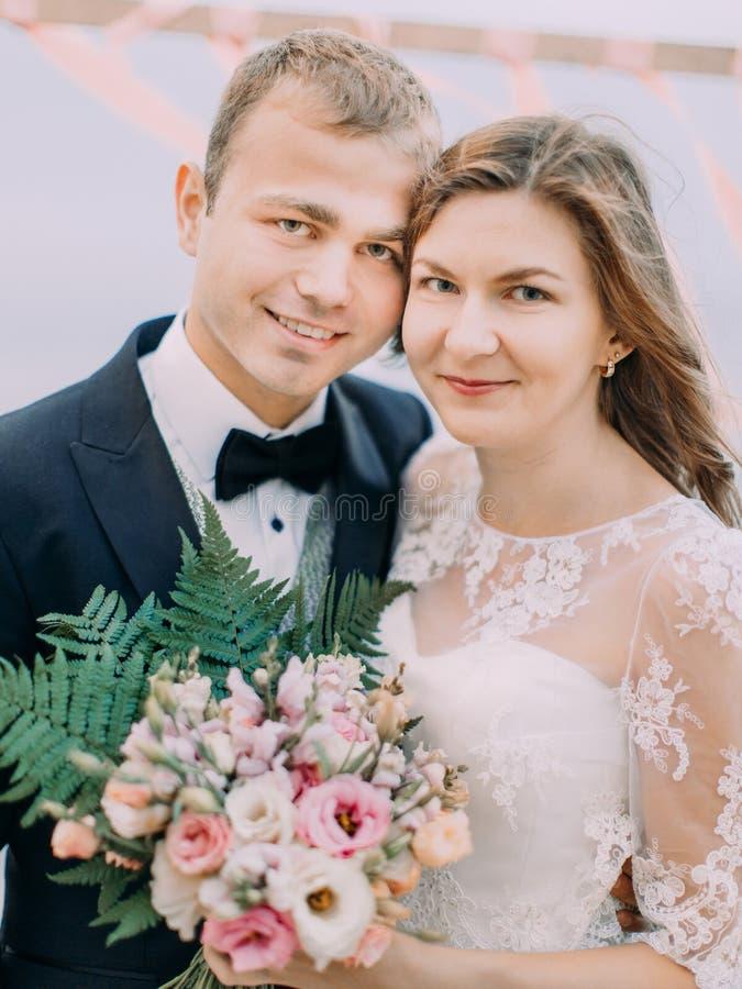 Das Nahaufnahmeporträt der lächelnden Jungvermählten Die Braut hält das bestandene Weiß und das Rosa der Hochzeit Blumenstrauß lizenzfreie stockfotografie