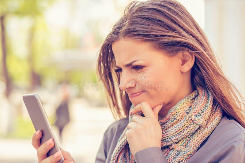 Das Nahaufnahmeporträt, das, skeptisch, unglücklich, die Frau simst am Telefon missfallen wurde mit Gespräch traurig ist, lokalis stockfoto
