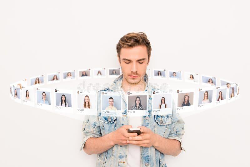Das nahe hohe Foto, das sitzt er interessiert ist, er sein Kerlgriff Smartphone, der online gewöhnt wird, Internet auszuwählen, a stockfotografie