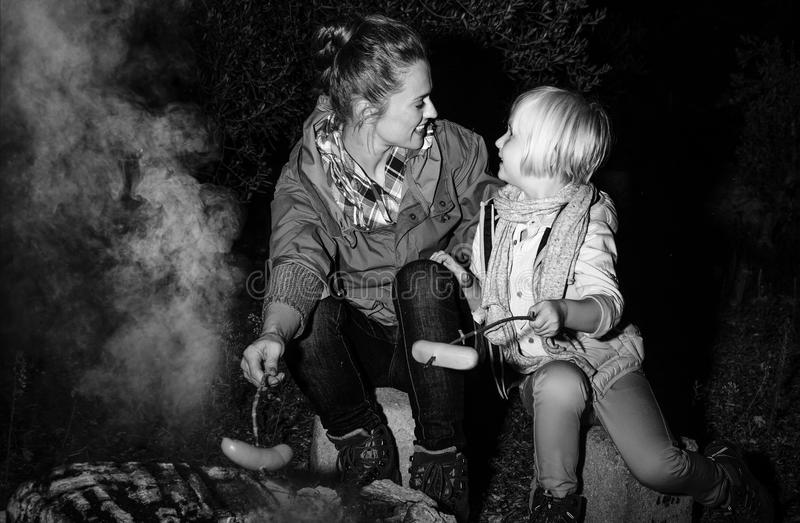 Das nahe Kampieren der Mutter- und Kinderreisenden feuern das Grillen von Würsten ab stockfoto