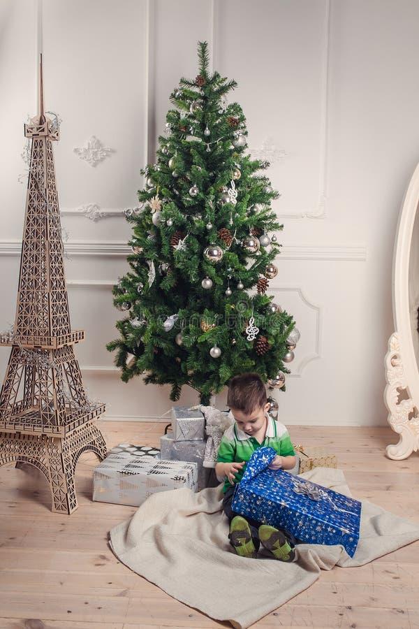 Das nette Baby, das unter verziertem Weihnachtsbaum sitzt, packt aus stockfoto